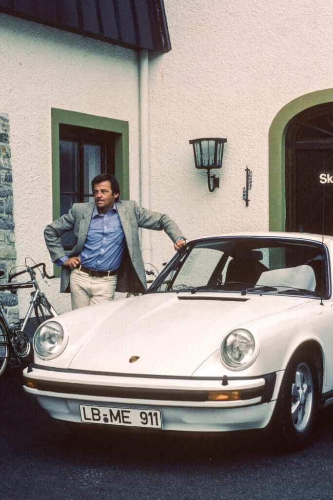 Hans Mezger mit seinem Grandprix-Weißen Porsche Carrera 3.0 vor dem Hotel Porschehof in Zell am See.